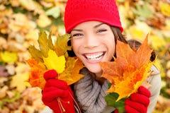 Foglie di caduta della tenuta della donna di autunno in foresta Fotografie Stock