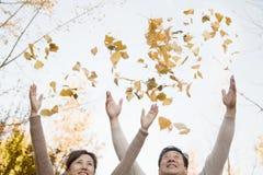 Foglie di lancio delle coppie mature nell'aria e divertiresi dentro in autunno Fotografia Stock