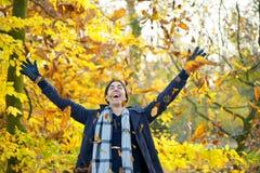 Foglie di lancio sorridenti felici dell'uomo con a braccia aperte dentro l'autunno Immagini Stock