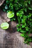 Foglie di menta fresca erba e calce sulla tavola di legno scura Vista superiore Fotografia Stock Libera da Diritti