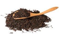 Foglie di tè asciutte in cucchiai di legno isolati su bianco Fotografia Stock