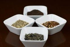 Foglie di tè asciutte in piatti quadrati con la riflessione Fotografia Stock Libera da Diritti