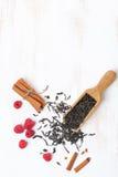 Foglie di tè, cannella e lamponi secchi su fondo bianco Fotografia Stock Libera da Diritti