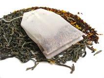 Foglie di tè con la bustina di tè Fotografie Stock Libere da Diritti