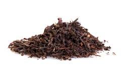 Foglie di tè nere asciutte isolate su bianco Immagine Stock