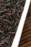 Foglie di tè nere in ciotola bianca Immagine Stock