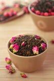Foglie di tè nere con i germogli rosa fotografia stock libera da diritti