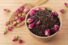 Foglie di tè nere con i germogli rosa fotografia stock