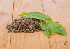 Foglie di tè sul pavimento di legno Fotografia Stock Libera da Diritti