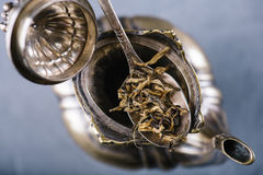 Foglie di tè verdi asciutte in cucchiaio d'annata del metallo sopra la teiera aperta Fotografie Stock