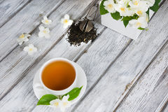 Foglie di tè verdi asciutte del gelsomino con i fiori freschi del gelsomino e la tazza bianca di tè verde su fondo di legno Vista Fotografie Stock