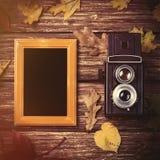 Foglie, macchina fotografica e struttura di autunno sulla tavola Immagine Stock