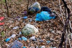 Foglie moderne di civilizzazione dietro le montagne ed i mucchi enormi di immondizia, che riguarda l'ecologia delle foreste e dei immagine stock