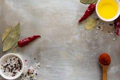 Foglie roventi dei piselli, del sale, dell'olio e della baia dei baccelli del peperoncino sul fondo culinario del metallo d'annat fotografie stock libere da diritti