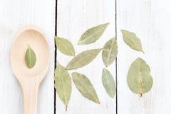 Foglie secche della baia e cucchiaio di legno su un fondo di legno piano Fotografie Stock