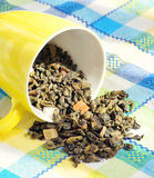 Foglie secche di tè verde in una tazza gialla Fotografie Stock