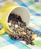 Foglie secche di tè verde in una tazza gialla Fotografie Stock Libere da Diritti