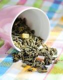 Foglie secche di tè verde in una tazza rosa Fotografie Stock Libere da Diritti