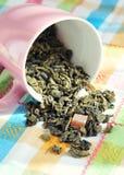 Foglie secche di tè verde in una tazza rosa Immagini Stock