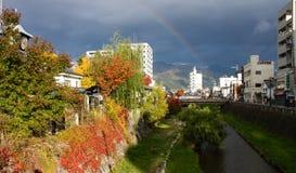 Foglie variopinte degli alberi alla riva del fiume in autunno fotografie stock