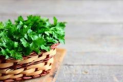 Foglie verdi del prezzemolo in un canestro Alte erbe antiossidanti Prezzemolo su fondo di legno d'annata con lo spazio della copi Fotografie Stock