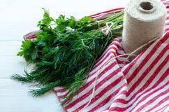 Foglie verdi dell'aneto e del prezzemolo sul tovagliolo di tela naturale su fondo di legno Immagini Stock Libere da Diritti