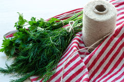 Foglie verdi dell'aneto e del prezzemolo sul tovagliolo di tela naturale su fondo di legno Immagine Stock