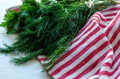 Foglie verdi dell'aneto e del prezzemolo sul tovagliolo di tela naturale su fondo di legno Fotografie Stock Libere da Diritti