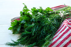 Foglie verdi dell'aneto e del prezzemolo sul tovagliolo di tela naturale su fondo di legno Immagini Stock