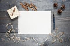 Foglio bianco di carta con composizione sulla struttura di legno scura Fotografia Stock