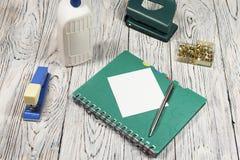 Foglio bianco di carta, del blocco note, della penna e di altra rifornimenti Fotografia Stock