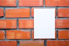 Foglio bianco di carta sui precedenti dei mattoni Fotografie Stock Libere da Diritti