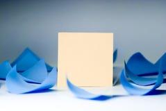 Foglio bianco giallo per le annotazioni in mezzo della menzogne blu di turbine degli strati Fotografia Stock