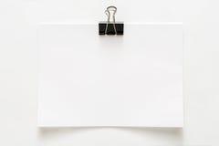 Foglio della carta in bianco allegato con la clip isolata su fondo bianco fotografia stock
