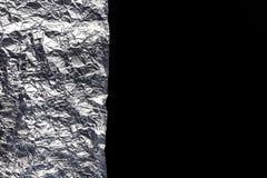 Foglio di alluminio d'argento su fondo nero, disposizione piana Immagine Stock