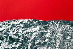 Foglio di alluminio d'argento su fondo rosso, disposizione piana Fotografia Stock