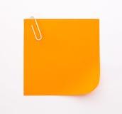 Foglio di carta arancio con la graffetta bianca su un backgroun bianco Fotografia Stock