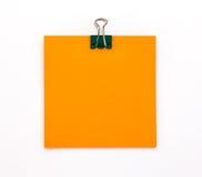 Foglio di carta arancio con la graffetta verde su un backgroun bianco Fotografia Stock Libera da Diritti