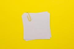 Foglio di carta bianco con la graffetta gialla su un backgrou giallo Immagine Stock Libera da Diritti
