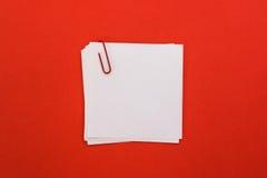 Foglio di carta bianco con la graffetta rossa su un fondo rosso Fotografia Stock Libera da Diritti
