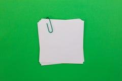 Foglio di carta bianco con la graffetta verde su un fondo verde Immagine Stock