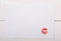 Foglio di carta bianco con un bacio su una tavola bianca Fotografie Stock Libere da Diritti