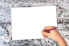 Foglio di carta bianco sulla tavola di marrone della quercia con la mano Immagini Stock Libere da Diritti