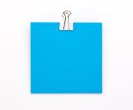 Foglio di carta blu con la graffetta bianca su un fondo bianco Fotografia Stock Libera da Diritti
