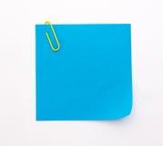 Foglio di carta blu con la graffetta gialla su un fondo bianco Fotografia Stock Libera da Diritti