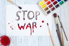 Foglio di carta con il testo di GUERRA di ARRESTO, i pennelli e l'acquerello p Fotografie Stock Libere da Diritti