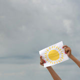 Foglio di carta con l'immagine del sole contro il cielo nuvoloso Immagini Stock Libere da Diritti