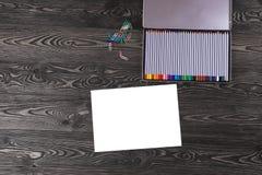 Foglio di carta con una matita sulla vecchia tavola scura Fotografia Stock