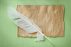 Foglio di carta d'annata la piuma sulla vista superiore del fondo verde Fotografia Stock