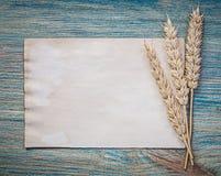 Foglio di carta del pane delle orecchie mature della segale d'annata sul bordo di legno Immagine Stock